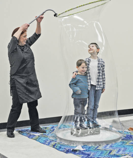 """Kids are enveloped in a giant bubble by """"The Bubble Lady,"""" Sue Durante, during an event at the Lorain County JVS."""