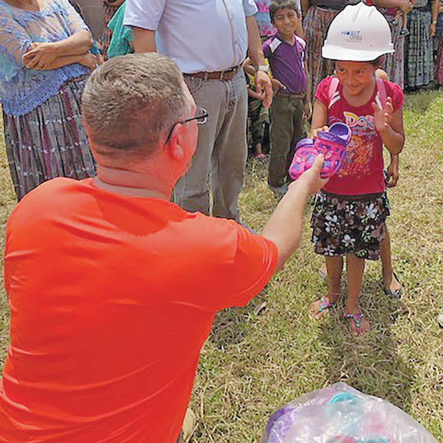 Brian Barr gives shoes to a little girl during his trip to Guatemala, where 17 Ohio Electric Cooperative linemen spent 18 days providing electricity to impoverished villages.