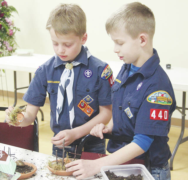 "Cub Scouts Michael Fox, 9, and Conner Hohn, 8, put together Easter gardens March 4 during ""messy church"" service at First United Methodist Church. Messy church aims to create a more casual atmosphere that any age group can enjoy."