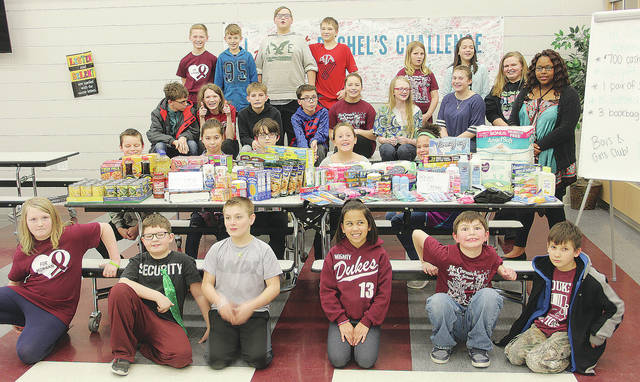 Boys and Girls Club members at McCormick Middle School prepare to hand over roughly $200 in household goods to Well-Help. Kids raised the money by playing a series of online brain-teaser games.