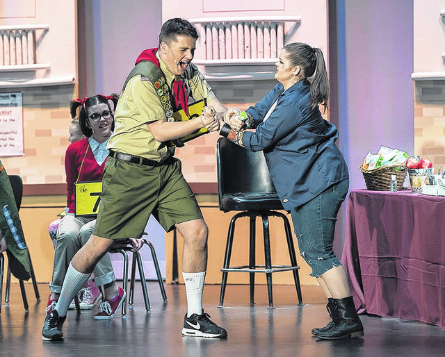 Annabella Miller (as Mitch Mahoney) tries to lead a distraught Jonathan Cwalina (as Chip Tolentino) off stage after he misspells his word.