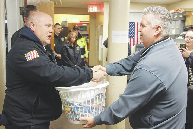 Wellington fire chief Mike Wetherbee is handed a gift basket by pastor Mike Goss in thanks for his department's role in fighting the area's opioid epidemic.