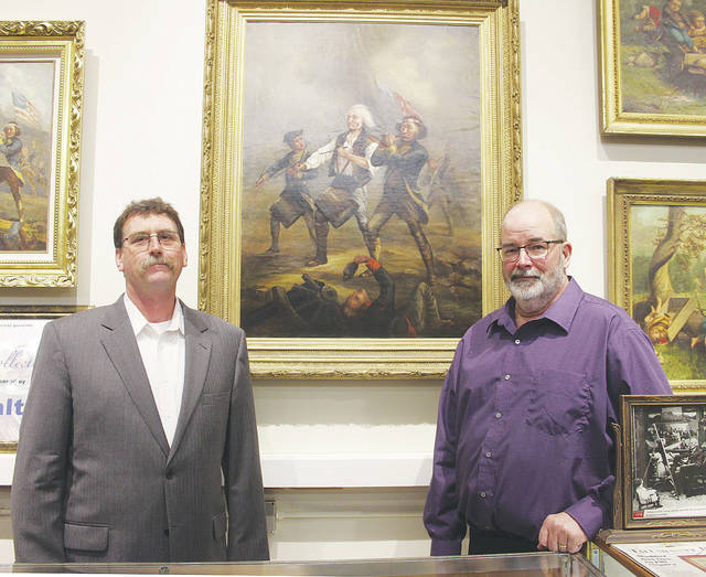 Scott Markel and Tim Rolfe, director and president of the Spirit of '76 Museum respectively, stand under the namesake painting thought to have been created for president Ulysses S. Grant. The work is one of 22 paintings by Archibald Willard loaned to the museum through October.