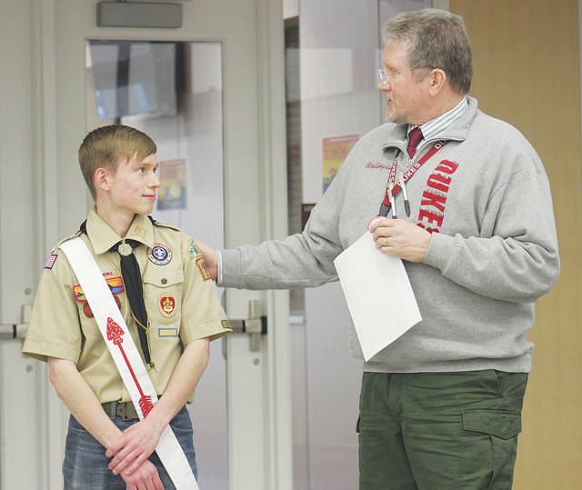 Westwood Elementary School principal Paul Holland thanks Boy Scout Paul Hornbeck for building two Buddy Benches for the playground.