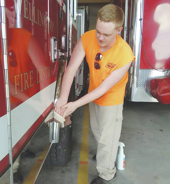 Sophomore Chase Knoll wipes down engines at the Wellington fire station.