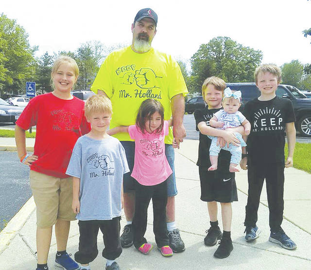 Parent Tim McGovern is joined Monday by Mackenzie Jerousek, Mark Davidson, Arianna McGovern, Preston Lasch, Tucker Lasch, and Aurora Lasch in showing support for principal Paul Holland.