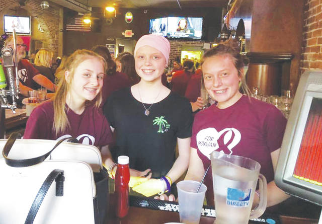 Morgan Lehmkuhl (center) welcomes guests Monday at Fort's Tavern during a fundraiser for her cancer treatment costs.