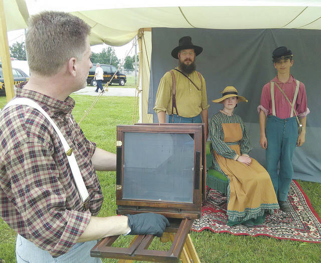 Photographer Mike Rhodes prepares to snap a tintype image of Doug Smith, Lindsey Carter, and Maddux Smith of Cuyahoga Falls.