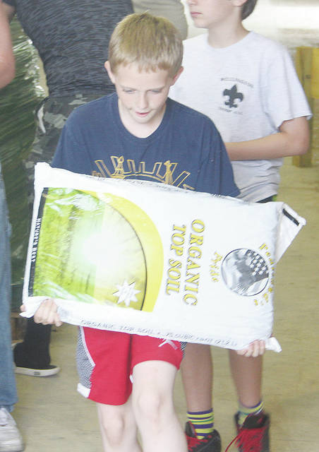 Logan Cuson carries a bag of soil June 7 as he and fellow Boy Scouts ship planting items to area seniors.