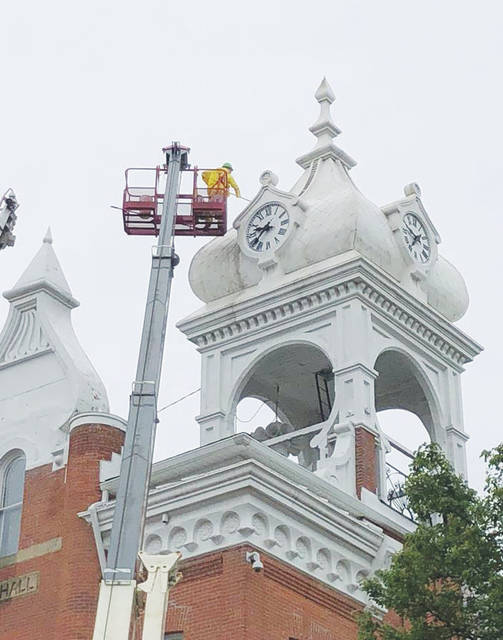 Scott Markel scrubs the exterior of village hall's clock tower Friday while several other pavement and painting projects took place around town.