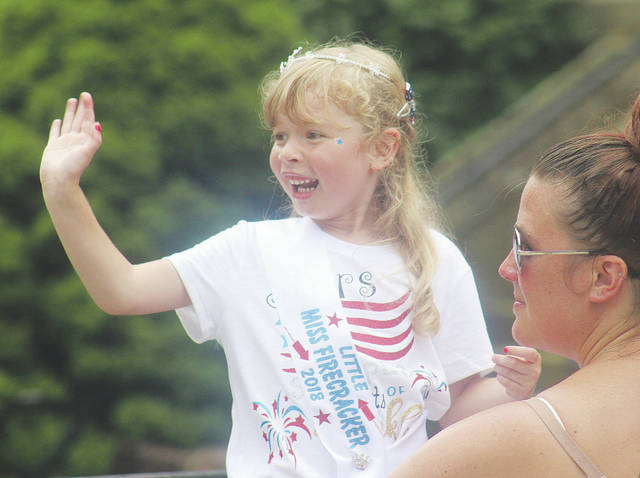 McKenna Piatrowski of Wellington waves to the parade crowd July 4 after being crowned Little Miss Firecracker 2018.