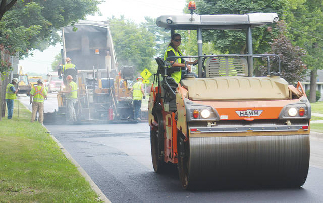 Crews smooth out new pavement on Rt. 58 Friday as a $1.7 million ODOT resurfacing project makes its way through Wellington.