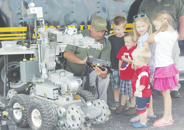 Lt. Randall Koubek, commander of the Lorain County Sheriff's Bomb Squad, shows how an explosive detecting robot works July 28 during a touch-a-truck event put on by Eagles Aerie 2051.