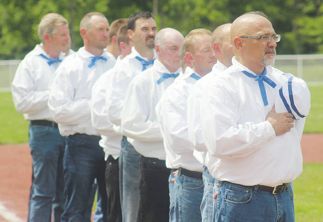 Mayor Hans Schneider and other members of the Wellington Village Gentlemen stand for the National Anthem Sunday during a vintage baseball game at Larry DeVoe Memorial Field.