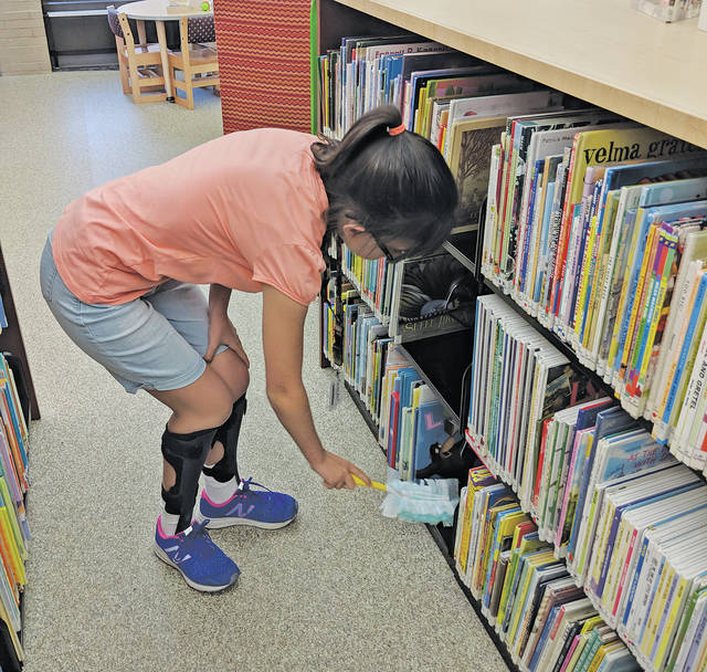 Sammi Given dusts shelves in the children's section at the Amherst Public Library, where she volunteers on Tuesday mornings. Everyone there knows Sammi, who is always eager to help.