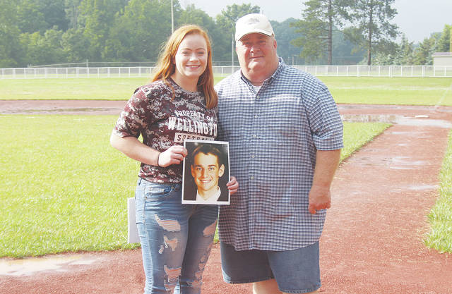 Rianna and Daniel Rosecrans hold a picture of family member Garrett Farr, who took his own life last September after a near lifelong battle with depression. Rianna is now raising funds to be put toward a college scholarship in Farr's name.
