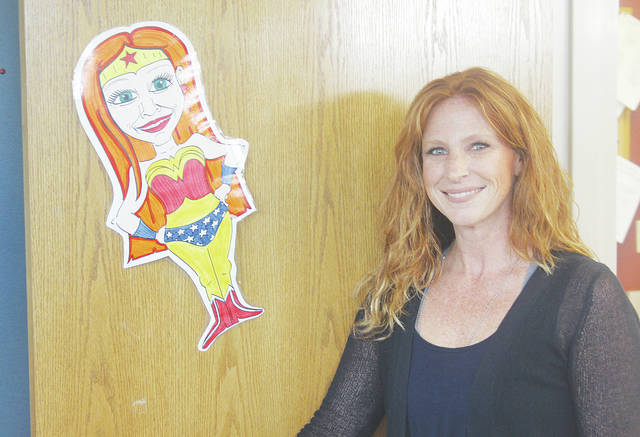 New Westwood Elementary School principal Erica Ward stands next to a Wonder Woman-inspired caricature of herself drawn by a teacher she worked with in Bucyrus. Ward was chosen in July to replace Paul Holland, who had filled the principal's seat since 2015.
