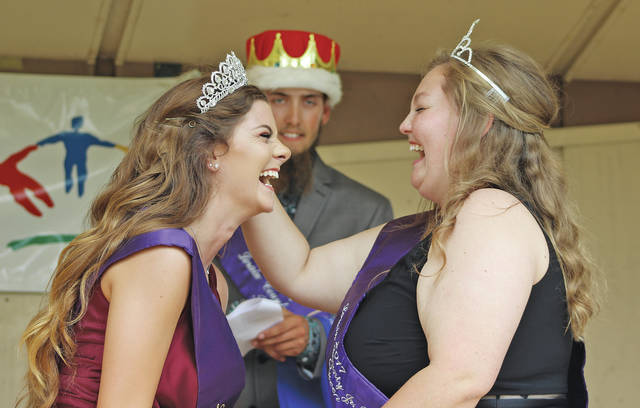 Last year's queen Bailey Wise shares a laugh with 2018 queen Jessica Urig after topping off her look with a tiara and a sash.