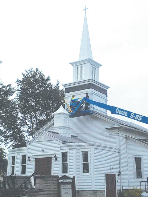 Workers put finishing touches on a new steeple Aug. 16 at Brighton Congregational Church.