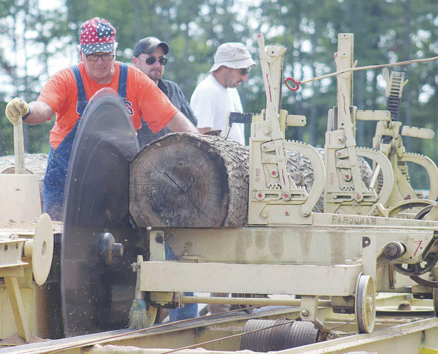 A steam engine powers a giant saw blade as it cuts lumber during the 47th annual LaGrange Engine Club Show at the Lorain County Fairgrounds.