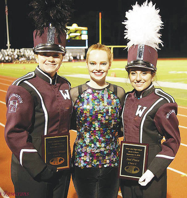 Dukes Marching Band band members Rianna Rosecrans, Grace Broome, and Samantha Cochick celebrate a pair of accolades earned Saturday during the 54th annual Avon Lake Band-A-Rama. Wellington took home first place for music and second place overall in Class C.