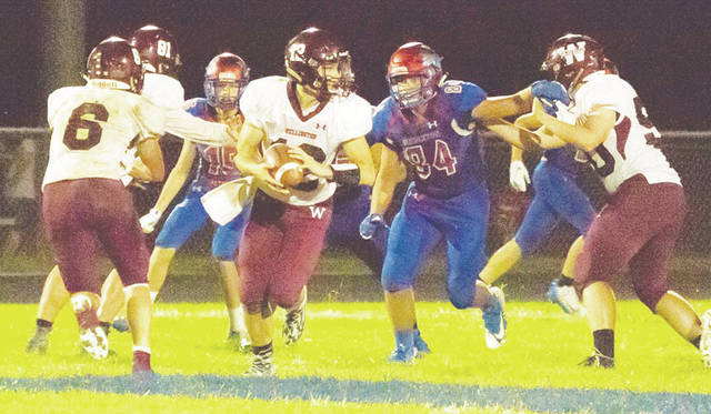 Dukes quarterback Ben Higgins drops back to pass in Friday's big loss to the Mapleton Mounties.