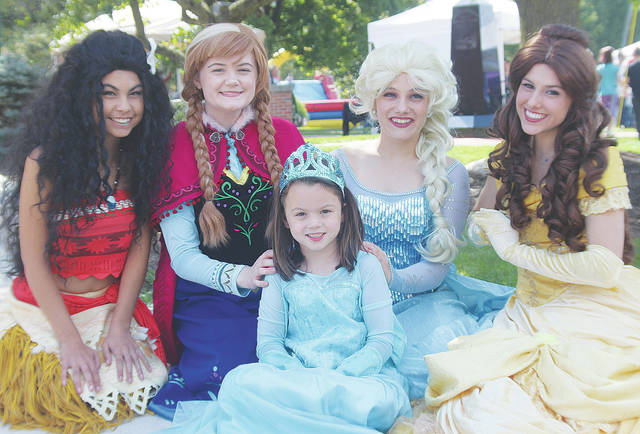 Five-year-old Taylor Land says hello to Disney princesses Mona, Anna, Elsa, and Belle during this past weekend's Fall in Love With Wellington festival.