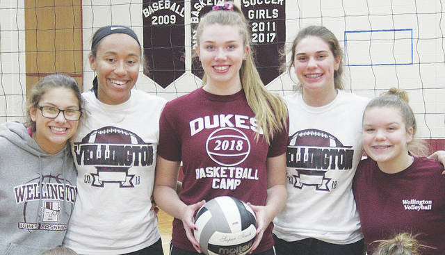 Alexis Lehmkuhl is surrounded by volleyball teammates Oct. 19 during preparation for tourney action. The senior went on to set a new Dukes career assists record over the weekend.