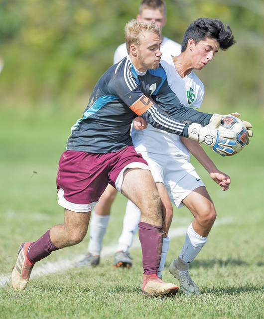 Dukes goalkeeper Stephen Del Campo gets to the ball ahead of an Elyria Catholic forward.