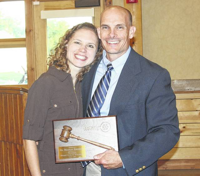 "<p class=""xmsonormal""><strong>Dr. Brad Baughman, outgoing President, is shown with his wife, Jessica, and his gavel award commemorating his 2 years as club president.</strong>"