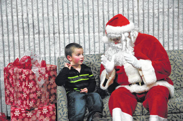 <strong>Carter Evans, age 5, tells Santa Claus what he would like for Christmas this year Saturday evening at the City of Englewood's annual Holiday Open House.</strong>