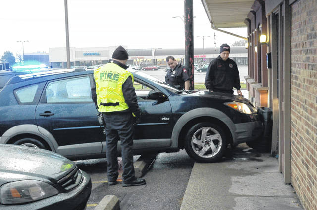 <strong>Englewood Police and Fire personnel check a motorist and her vehicle at CR Butts Discount Tobacco after the driver failed to brake and struck the building shortly after 4:30 p.m. Wednesday.</strong>