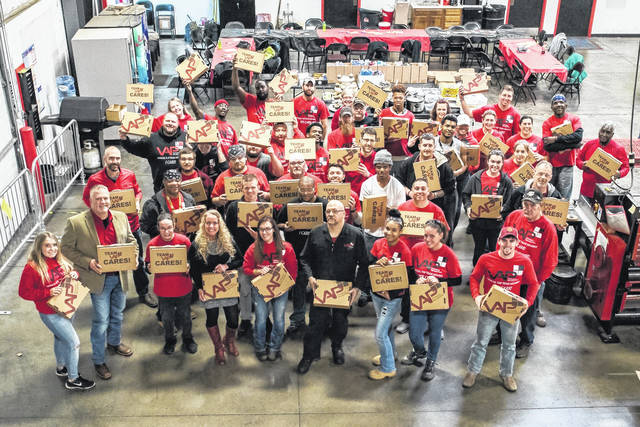 <strong>Value Added Packaging employees holding the Care Packages they assembled for St. Vincent de Paul.</strong>