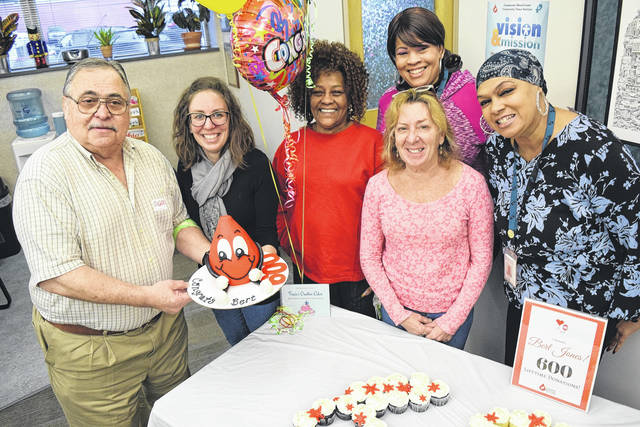 <strong>Bert Jones celebrates his 600th lifetime donation with the Community Blood Center staff.</strong>