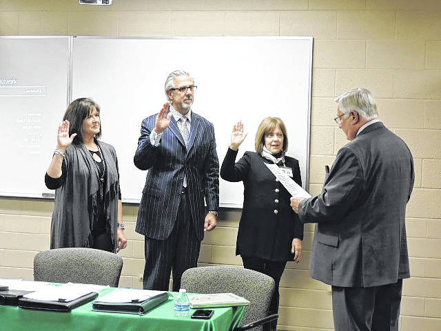 <strong>Tom Walker administers the oath of office to Jane Woodie (left), Chris Pulos and Linda Blum.</strong>