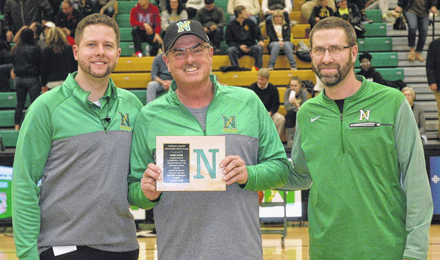 <strong>Randy Butler (center) was presented with a plaque for his 25 years of dedicated service as the head groundskeeper at Northmont prior to the boys varsity basketball game Friday. He is flanked by Athletics Director Micah Harding (left) and Assistant Athletics Director Jim Smith.</strong>