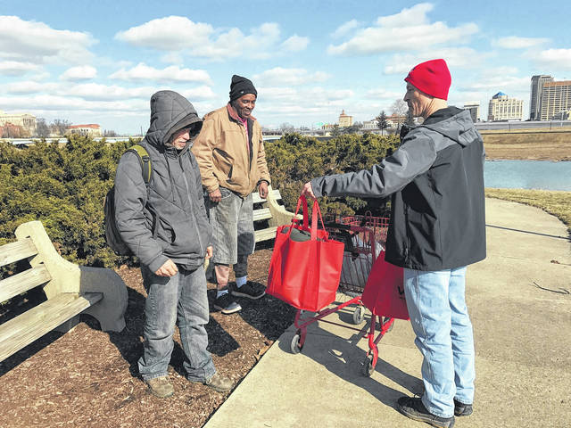 <strong>A member of Team VAP hand delivers Warm Care Packages to homeless men along the Great Miami River in downtown Dayton.</strong>