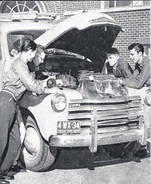 <strong>A Randolph High School teacher and students working on a late 1950s Chevrolet pickup displaying a Randolph Township Fire Department sticker in the lower right hand corner of the windshield.</strong>