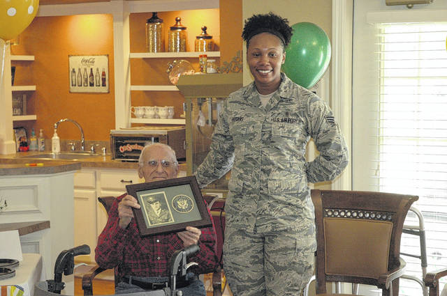 <strong>Charles &#8220;Skip&#8221; Inskeep holds the plaque commemorating his service in the U.S. Army during World War II. Camille Gentry of the U.S. Air Force presented the plaque to Inskeep during his 100<sup>th</sup> birthday celebration.</strong>