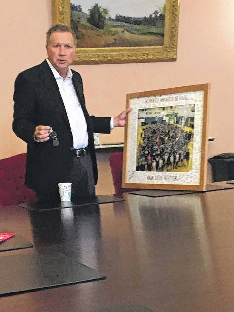 "<strong>Governor John Kasich holding the framed photo of the March 14 ""walk-in"" held at Northmont High School and signed by students.</strong>"