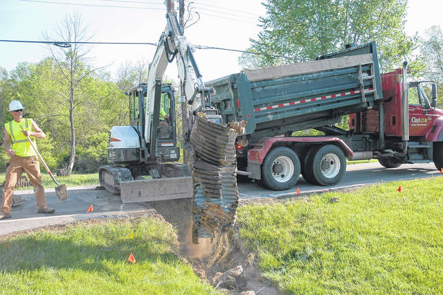 <strong>Clayton street department workers are shown working to tear out a recently discovered collapsed corrugated metal pipe on Old Salem Road in front of Covenant Baptist Church. The pipe collapse created a sinkhole that extended halfway across the roadway beneath the pavement.</strong>