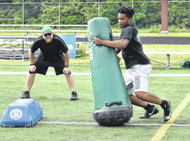 <strong>Defensive Line Coach John Brands looks on as Marcus Burkes fights past a blocking dummy during a pass rush drill Saturday morning.</strong>