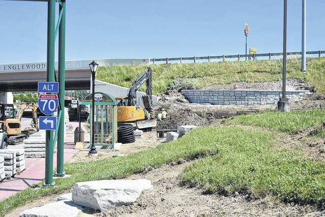 <strong>Workers with Outdoor Enterprise have started installing flat limestone rocks (foreground) at the corner of Rockridge Road and Main Street as well as decorative, curved retaining walls on the side of the hill below Interstate 70.</strong>