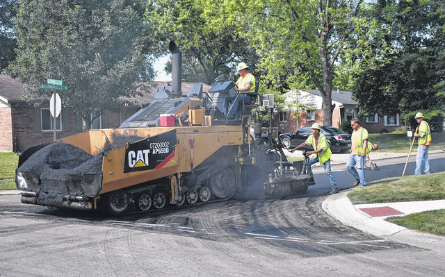 <strong>Workers with the John R. Jurgensen Company are shown laying asphalt Wednesday morning on Baldwinhills Drive.</strong>