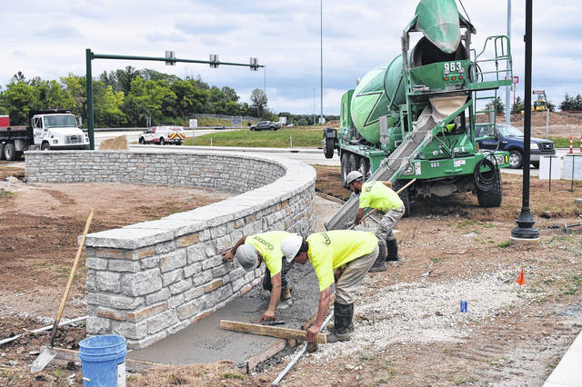 <strong>Workers prepared cement on Monday for the installation of brick pavers that will be placed in front of the retaining wall at the end of the I-70 West exit ramp at Main Street.</strong>