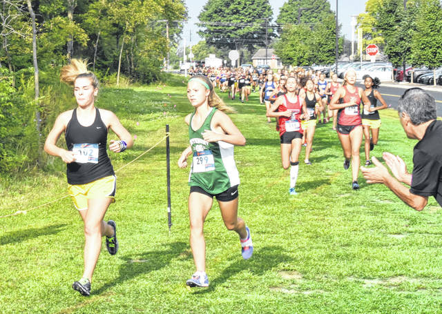 <strong>Freshman Chloe Knick (299) runs alongside eventual fifth place finisher Savannah Lowe of Centerville on the opening leg of the Northmont Invitational.</strong>