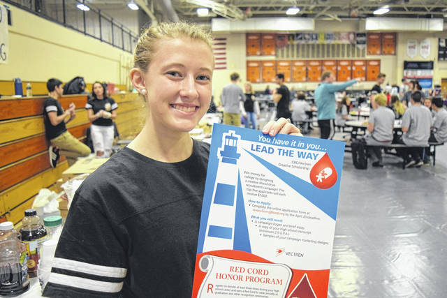 <strong>Student Council volunteer Calli Hess displays the Lead The Way Scholarship poster at the Beavercreek High School blood drive.</strong>