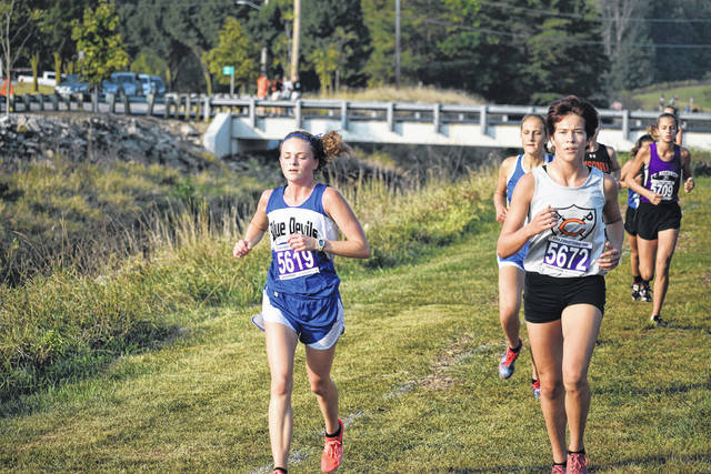 Brookville senior cross-country captain Emilie Penick is shown passing several runners to help the girls to a three-point victory at the Versailles Tour de Sewer Invitational this past Saturday.
