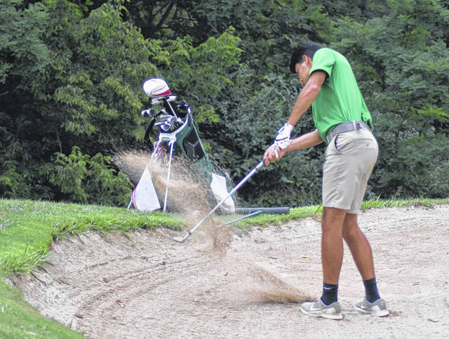 <strong>Justus Thomas punches the ball out of a bunker on the ninth hole at Meadowbrook vs. Miamisburg.</strong>