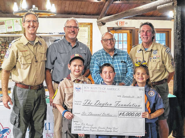Three scouts from Pack 47 presented a fundraiser check in the amount of $6,000 from the Miami Valley Council to Mike Parks of The Dayton Foundation (back row, third from the left) to be used for the Greater Dayton Disaster Relief Fund and the Dayton Oregon District Tragedy Fund. Scouts shown in the front row (from left) are Tim Moler, Calen Robinson, Kalei Robinson.